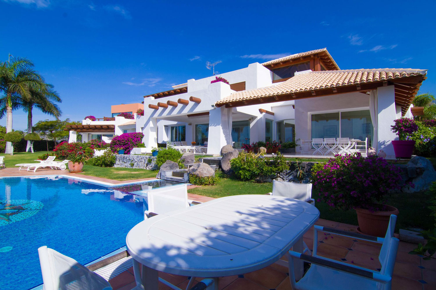 The modern residence is surrounded by beautiful gardens with an infinity pool overlooking the countryside, the sea, and the neighboring island of La Gomera. It is close to many local amenities and the delightful fishing village of La Caleta.